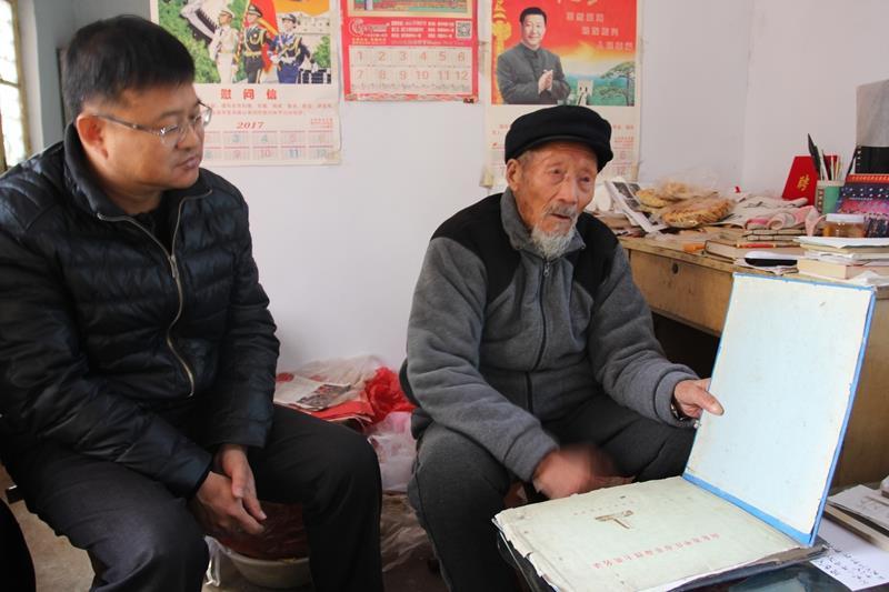 向来访者介绍他保存数十年载有烈士的名字的英烈册.JPG