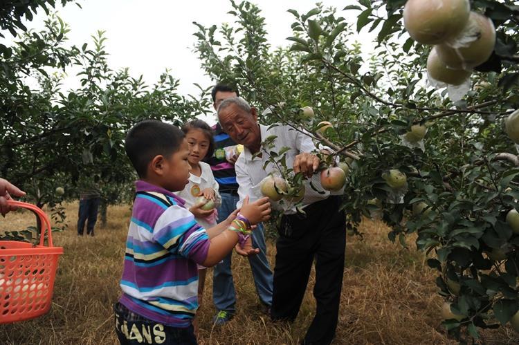 李言成和孩子们一起从事农事体验.JPG