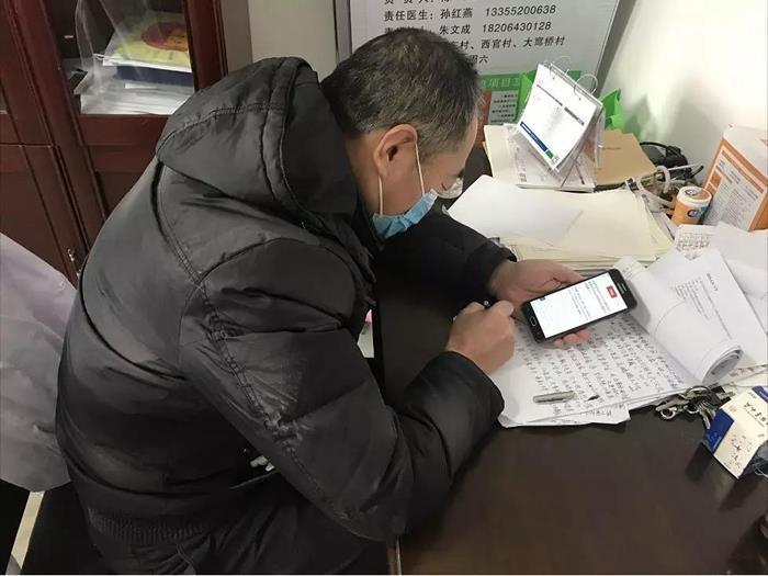 李信发工作之余不忘关注疫情动态.jpg