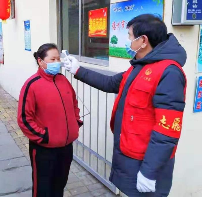德州市德城区兴文社区五老志愿者为进入小区人员测量体温.jpg